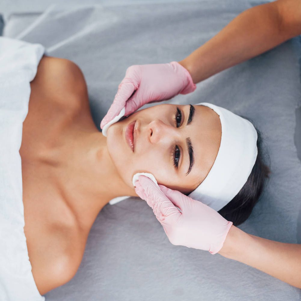 Close up view of woman that lying down in spa salon and have face cleaning procedure.