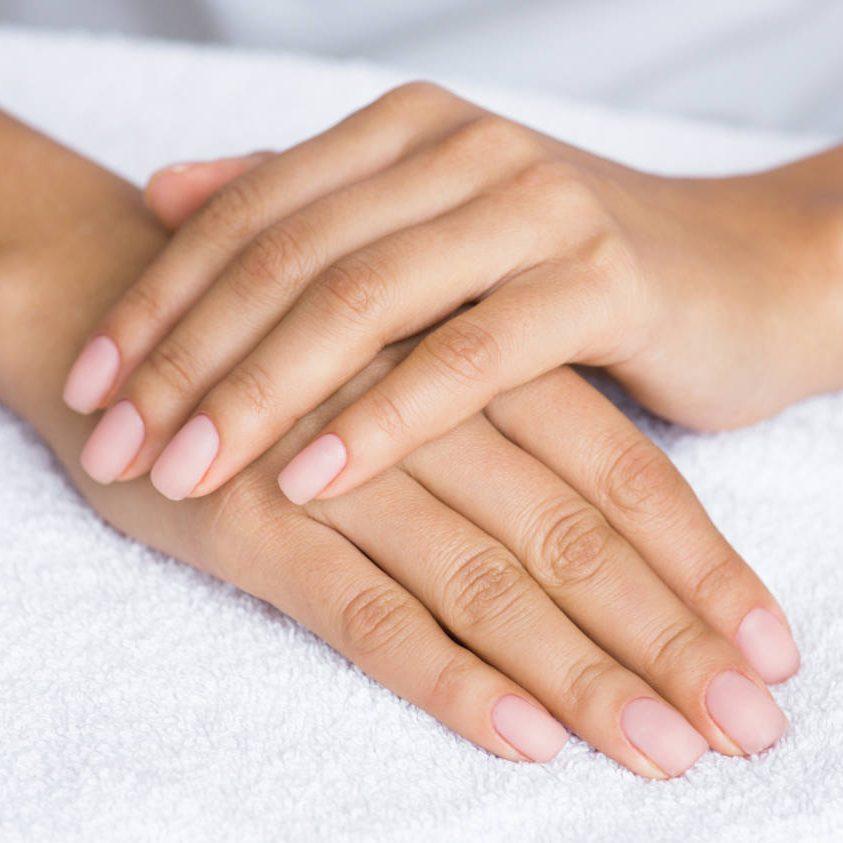 Nude manicure. Female hands on white towel, closeup
